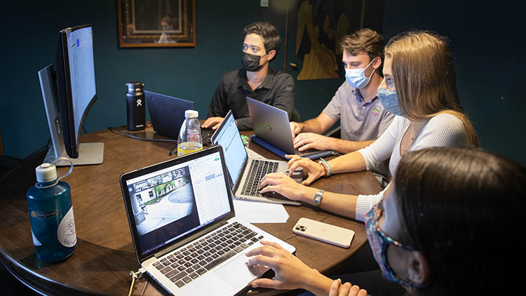 Four students with laptops looking at a central monitor