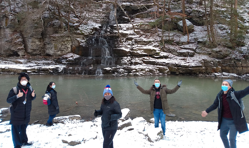 Five students on a snowy winter hike in a gorge with a stream