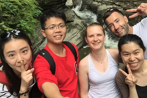 Five smiling students standing infront of a waterfall