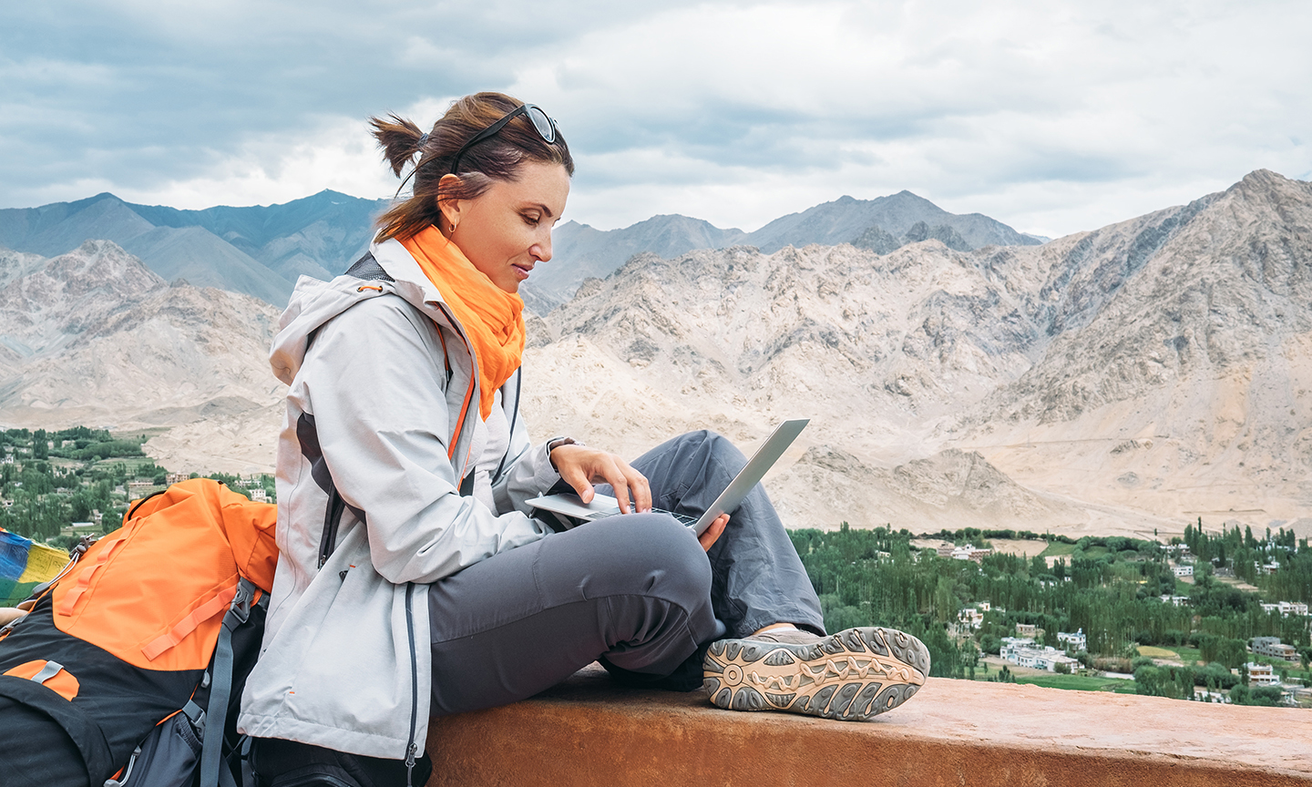woman sitting on wooden bench with laptop in hand and mountains in the distance
